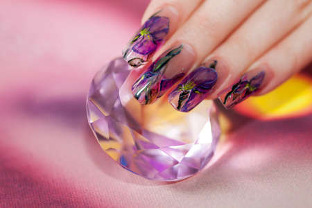 Fingers with long acrylic fingernails and beautiful manicure touch a shining diamond