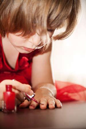 uñas pintadas: La muchacha de cuatro años en un vestido rojo con pintura interés en las uñas con esmalte de uñas Close-up