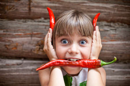 hellion: Funny young girl with a red hot chili pepper in her mouth showing red devil horns