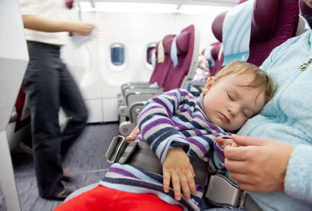 Flying with children  Mother and sleeping two year old baby girl travel on a commercial airliner Banque d'images