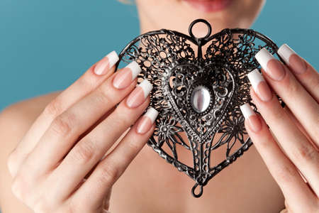 Human hands with beautiful manicure hold a openwork heart photo