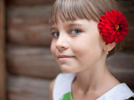 log hair: Attractive seven-year old girl with a red flower in her hair in front of a log wall Stock Photo