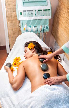 Stone therapy. Woman getting a hot stone massage in spa salon  photo