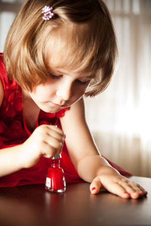 Four-year girl in a red dress with interest paint on nails with nail polish