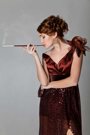Retro-style glamor portrait of young beautiful brunette woman smoking cigarette  Over grey background photo