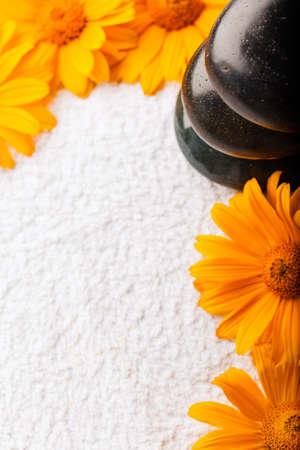 Spa stones on white towel with orange golden-daisy flower photo