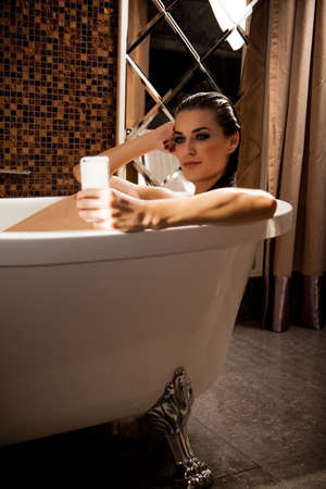 wet nude: Joven y bella mujer est?entada en el ba? tiene videochat por tel?no inteligente en el ba?e su casa