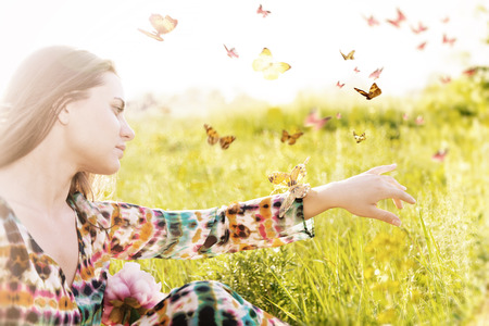 Summer mood. Girl sitting in a meadow in a swarm of flitting butterflies.