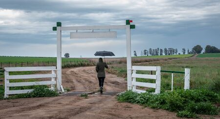 A woman walking hurried om the farm road. Stock Photo