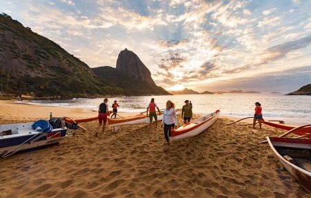 Rio de Janeiro, Brazil - August 17 2013: Group of women preparing outrigger canoes to go to the sea. Photo taken in Red beach, next to the sugarloaf mountain.