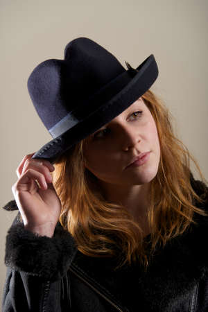 head tilted: Redhead in black hat with head tilted