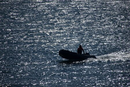 arctic waters: Man driving inflatable in backlit Arctic waters