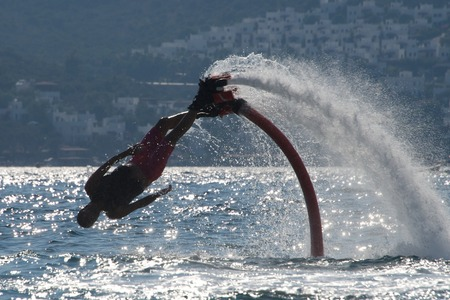 diagonally: Flyboarder diving diagonally headfirst into backlit waves