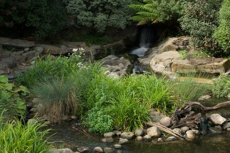 riverbed: Blurred waterfall and rocky riverbed in sunshine Stock Photo