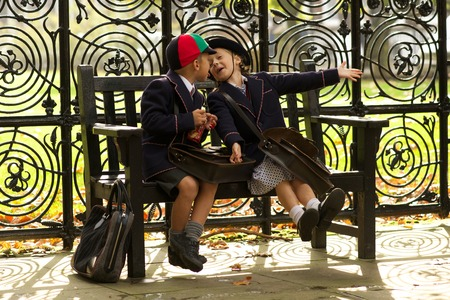 blond boy: Brother and sister playing on wooden bench Stock Photo
