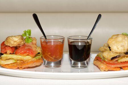 appetiser: Two sauce glasses between tempura fried vegetables Stock Photo