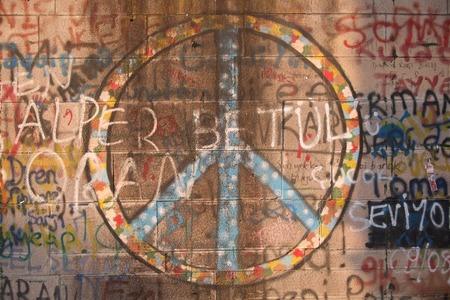peace symbol: Peace symbol and graffiti spray-painted on wall