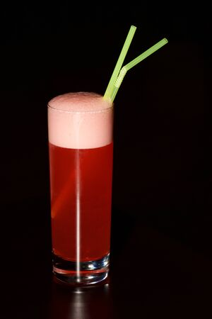 sherbet: Glass of red sherbet with green straws
