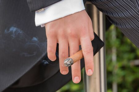 leans on hand: A man in black tails and grey pinstripe trousers is holding a lit cigar between his fingers as he leans against a metal railing. This is a close-up of the hand and cigar with smoke trailing from it. Stock Photo