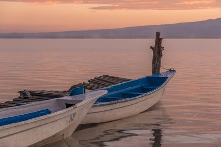 lake naivasha: Two blue and white wooden boats are moored by a wooden dock on a lake at dawn. In the background is a low hill with pink and purple clouds above it. Stock Photo