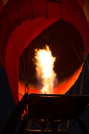 long tongue: A burner is shooting out a long tongue of flame as it starts to inflate a red and orange hot air balloon in the darkness before dawn.