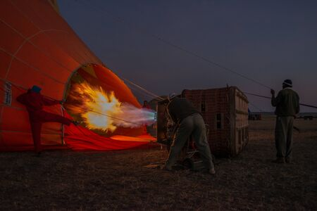 long tongue: Three men are helping to inflate a hot air balloon before dawn. Someone inside the basket is using the burner, which is shooting out a long tongue of flame.