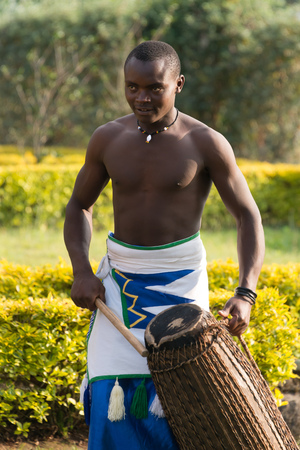 barechested: A bare-chested black man in blue, white and green tribal dress and wearing a necklace plays a drum. Behind him is a garden with several hedges and a tree.