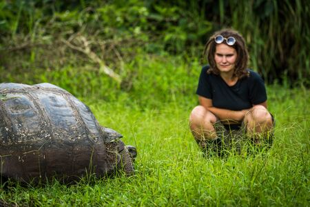 girl squatting: Woman staring intensely at Galapagos giant tortoise