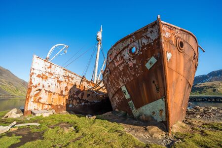 beached: Two rusty old whalers beached on shore Stock Photo