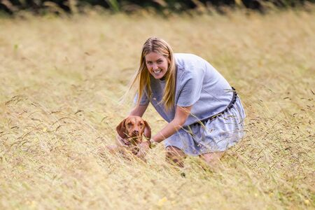 hungarian pointer: Woman holding Hungarian Vizsla in tall grass