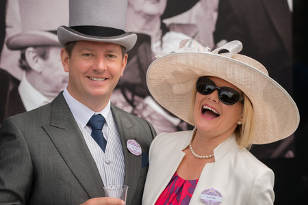 A man in grey morning dress with a top hat, blue tie and matching handkerchief and wearing a badge for the Royal Enclosure at Ascot is standing next to his wife, who is wearing a colourful dress under a cream jacket with a pearl necklace and earrings, sun Standard-Bild