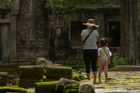 Mother and daughter stand on mossy flagstones