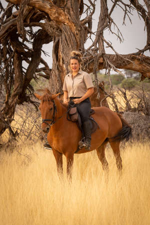 Blonde horsewoman in savannah rides towards camera