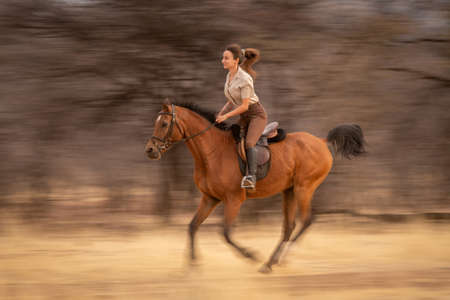 Slow pan of brunette riding past trees