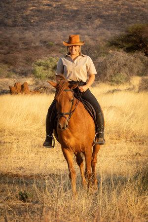 Smiling blonde on horseback with bushes behind