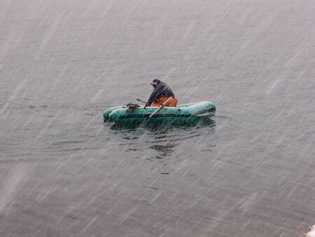 Ichthyologist on the inflatable boat recovers nets from the sea in heavy snowfall