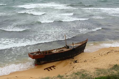 Korean fishing boat wreck on sandy sea beach after the storm. Broken boat of poor north korean fishermen.