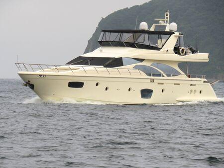 Luxury pleasure motor boat sailing along the steep green coast Stock Photo