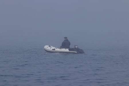 Fisherman in inflatable fishing boat with outboard motor moving in the dense fog. Stock Photo