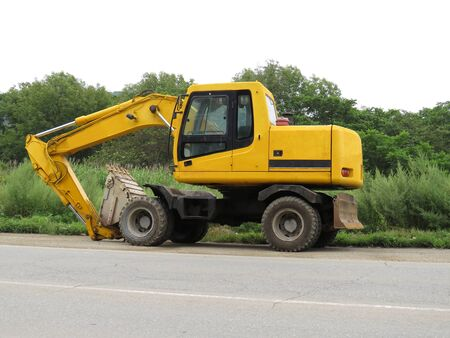 Yellow excavator parked on the roadside on the green woods background
