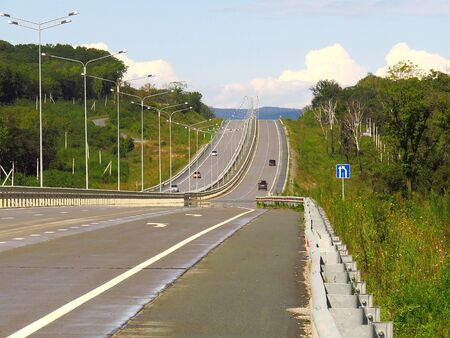 Well-maintained landscaped highway in the woods in sunny day Stok Fotoğraf
