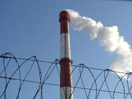 Big factory chimney smoking with white smoke and barbed wire fence on the clean blue sky background