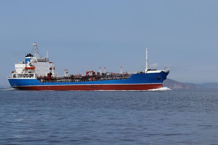 Tanker ship moving in sea full speed ahead on coast background. Sunny day, calm blue sea, blue sky.