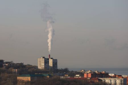 City district with big factory chimney smoking with white smoke. Vladivostok, Far East Russia. Reklamní fotografie