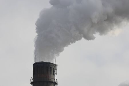Factory chimney smoking with dense white smoke. Industrial pollution of air, electric plant emission, environment ecology problem.