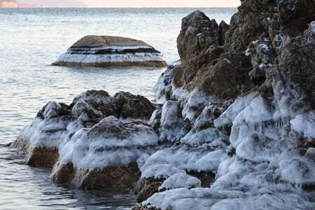 Icing on the coastal rocks. New winter ice frost on the sea shoreline.