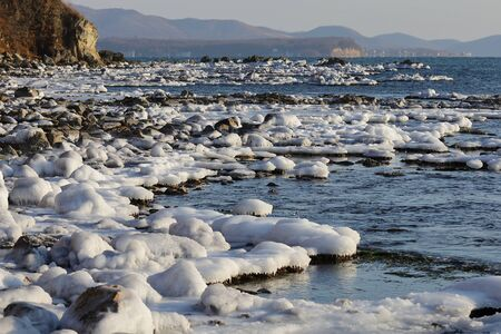 Ice caps on stones of the sea coast. Winter landscape of coastal line. Icing on shore rocks in low winter temperature. Reklamní fotografie