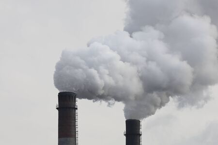 Factory chimneys smoking with dense white smoke. Industrial pollution of air, electric plant emission, environment ecology problem.