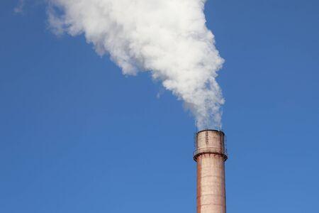 Fabryczne palenie komina z gęstym białym dymem na tle błękitnego nieba. Zanieczyszczenia przemysłowe powietrza, emisja z elektrowni, problem ekologii środowiska.