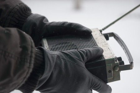 man in winter gloves is holding an old radio. Search for lost winter tourists concept. Imagens